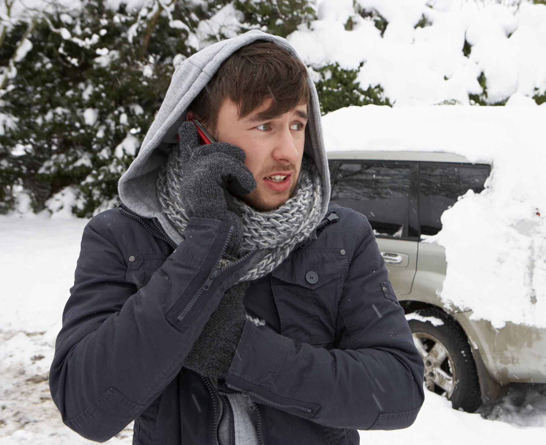 Young man in snow with broken down car
